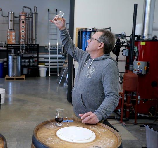 Jeff Glenn studies a sample of amaro, a bitter Italian liqueur, at Highside Distilling on Bainrbidge Island.