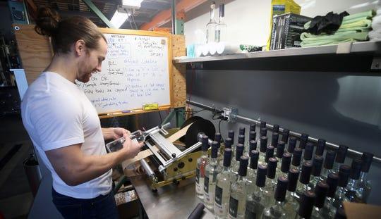 Matt Glenn, of Highside Distilling on Bainbridge Island, applies a label to one of the distillery's gin bottles.