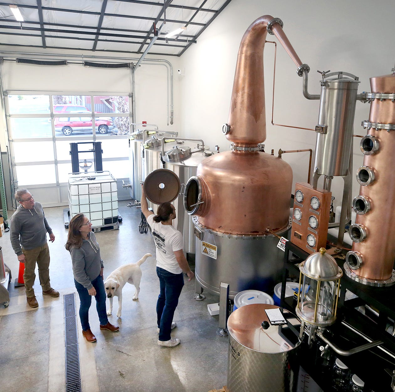 Jeff, Helen, and Matt Glenn , looking inside the special still, with dog Tucker are starting up a small craft distillery – Highside Distilling, on Bainbridge Island where they focus on making single malt whiskey, gin and amaro.