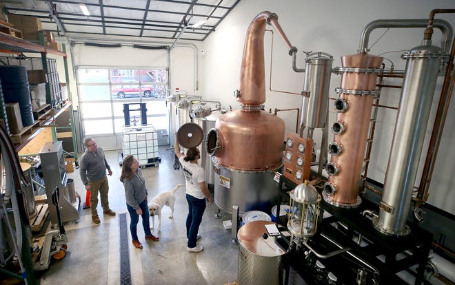 Jeff, Helen and Matt Glenn — looking inside a still with dog Tucker — are starting up a small craft distillery, Highside Distilling, on Bainbridge Island, where they focus on making single-malt whiskey, gin and amaro.