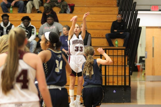 Junior Miriam King puts up a three-pointer from the corner against Roberson in the Warlassies' season opener.
