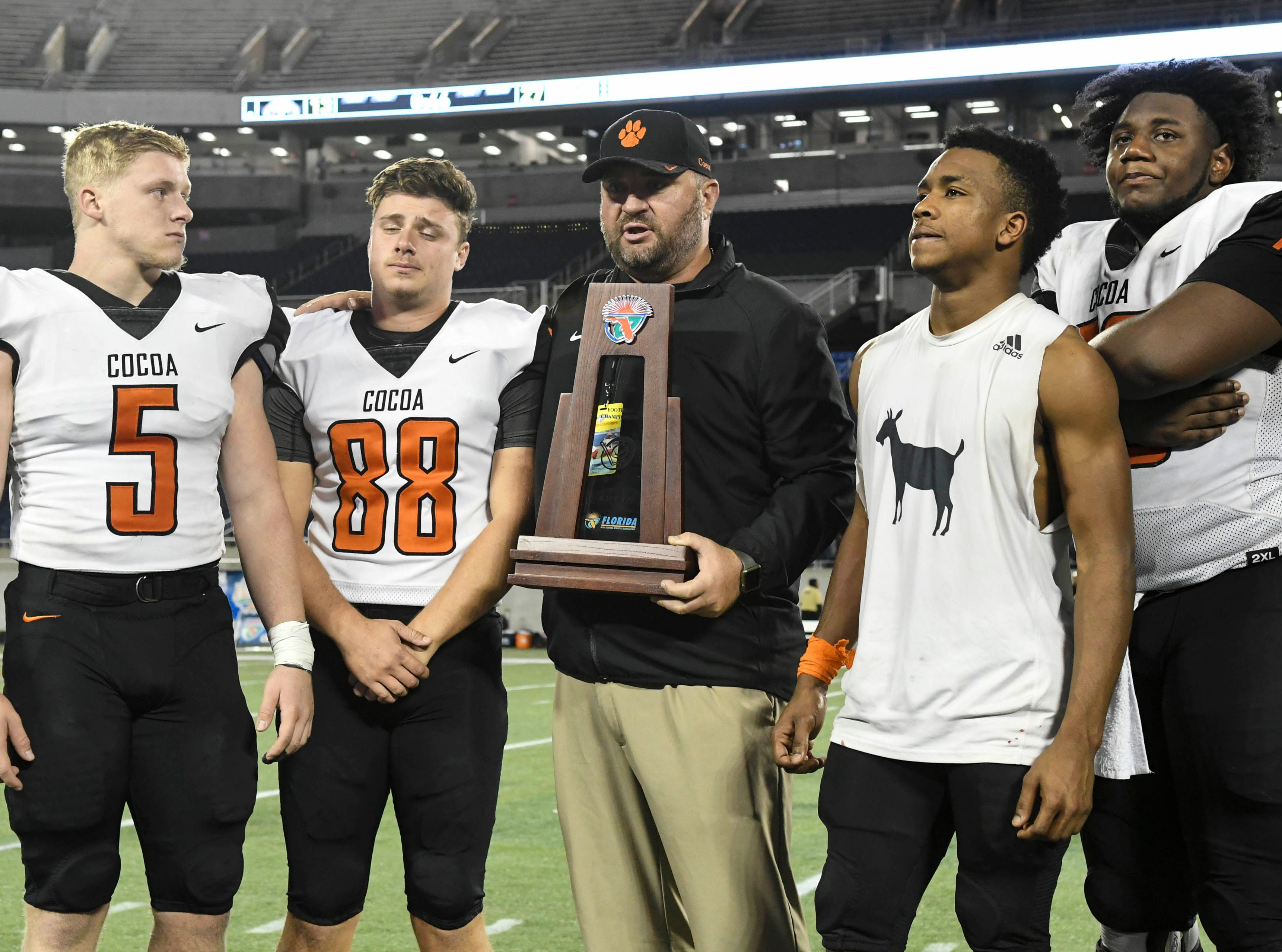 Coach Ryan Schneider and seniors Brock Holland, Alex Petruzzello, Willie Gaines and Richie Leonard stand with the Class 4A runner up trophy after Thursday's Class 4A football state championship.