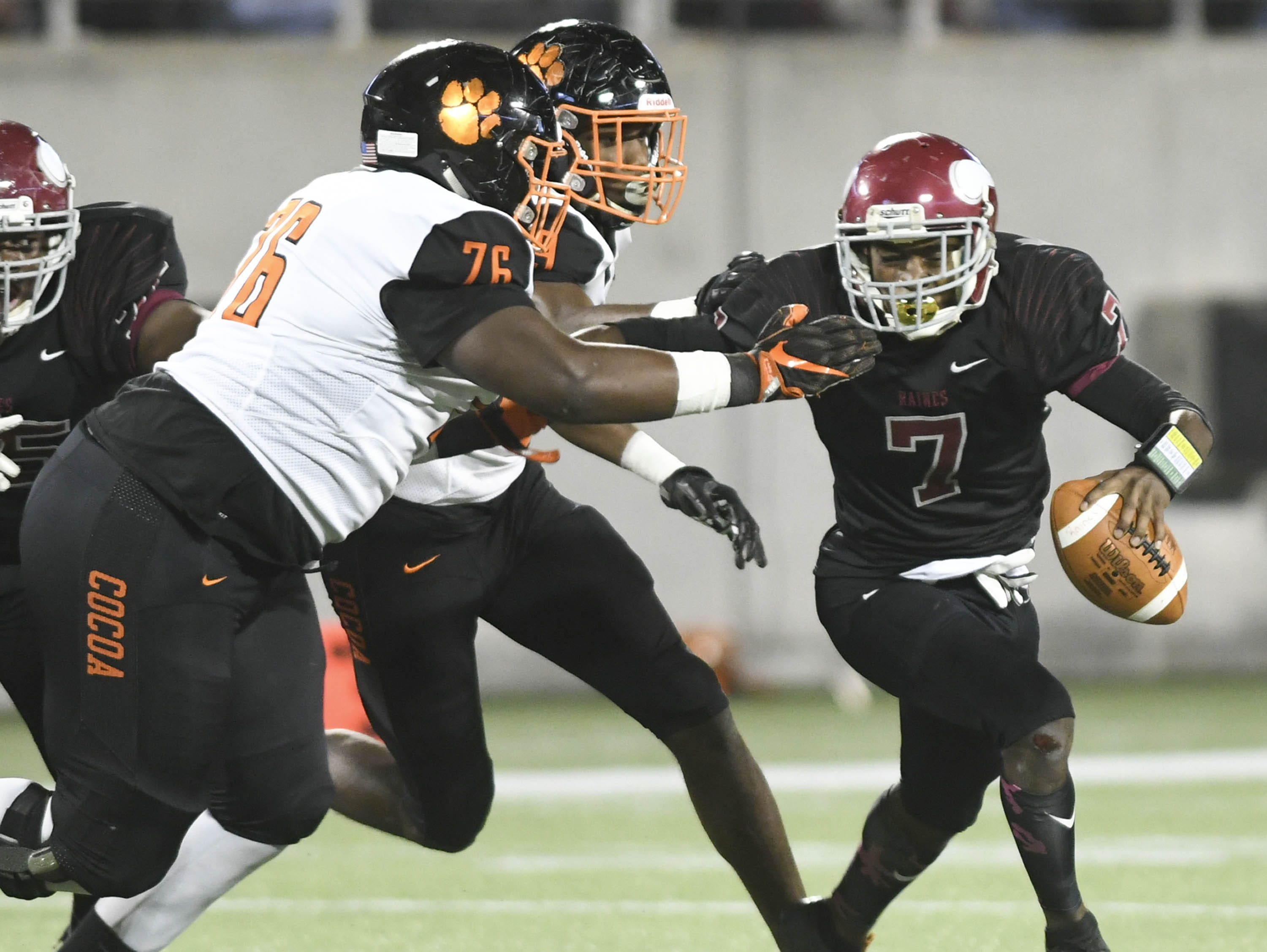 Raines QB jacorey Rivers is chased down by Richie Leonard (76) and Caziah Holmes of Cocoa during Thursday's Class 4A football state championship.