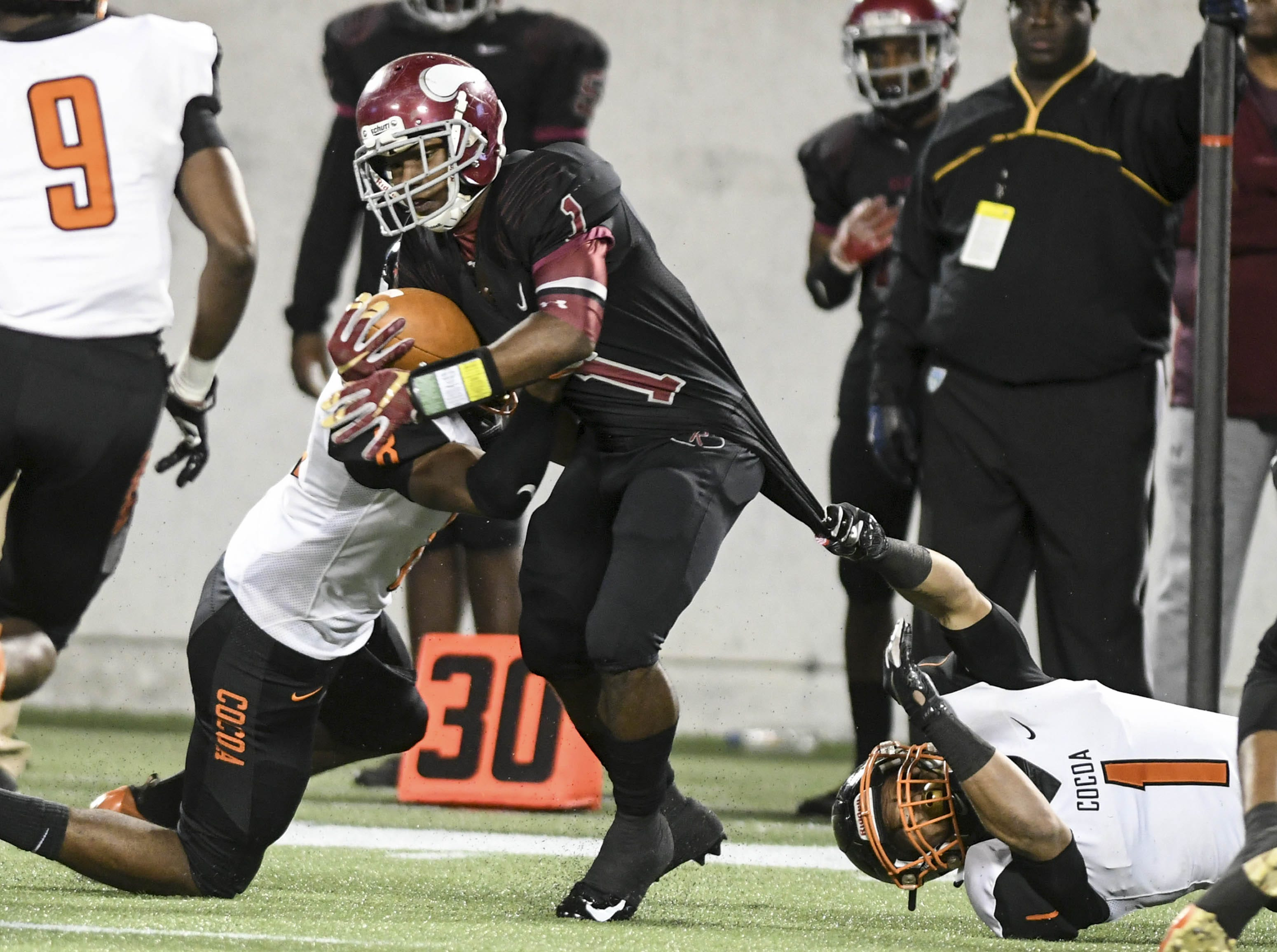 Brandon Marshall of Raines is dragged down by Allen Pierce and Willie Gaines of Cocoa during Thursday's Class 4A football state championship.