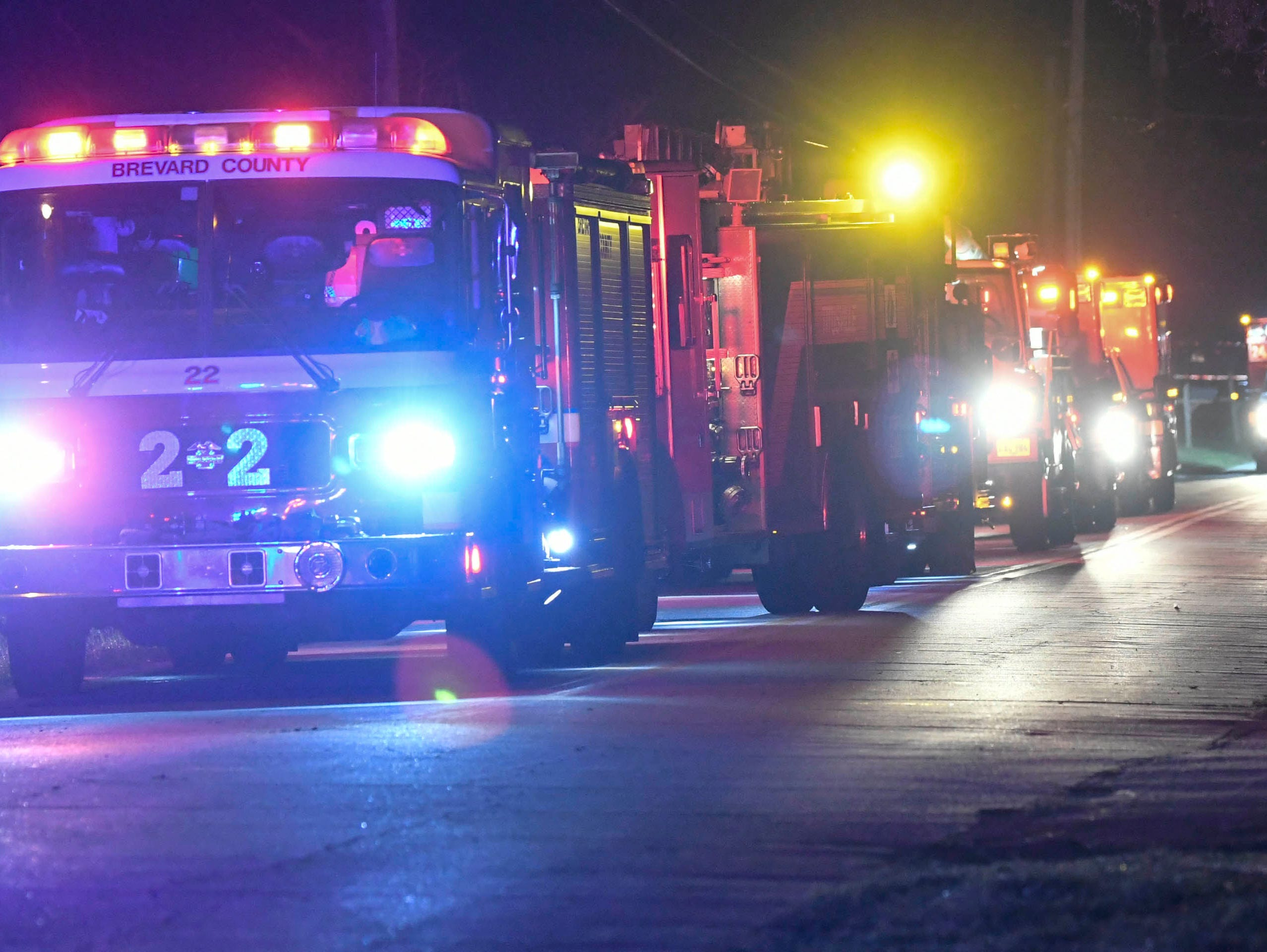 Brevard County fire and rescue vehicles park near a house fire on Brockett Rd. In Mims early Friday morning. The house was heavily damaged in the blaze.