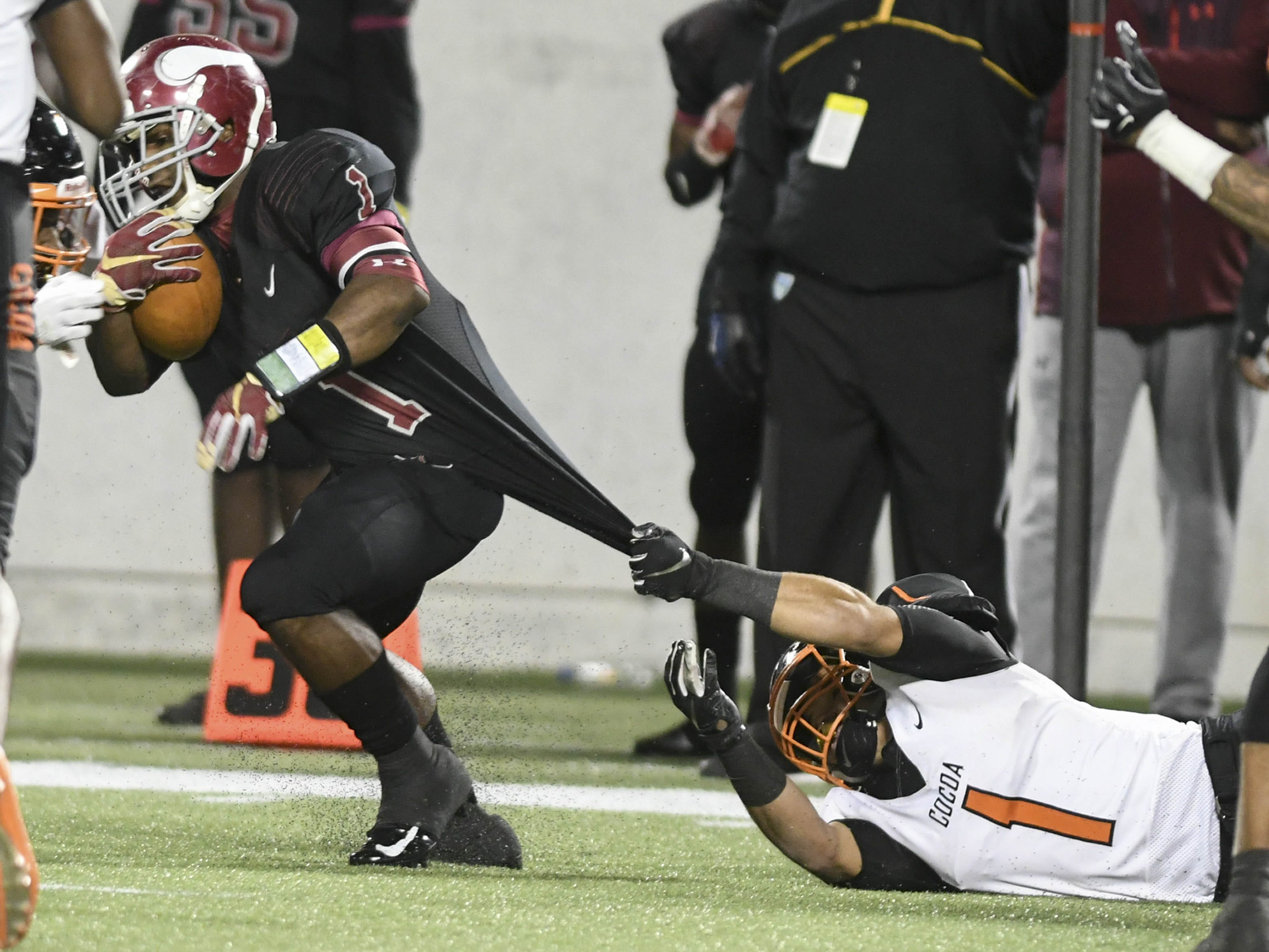 Brandon Marshall of Raines is dragged down by Allen Pierce of Cocoa during Thursday's Class 4A football state championship.