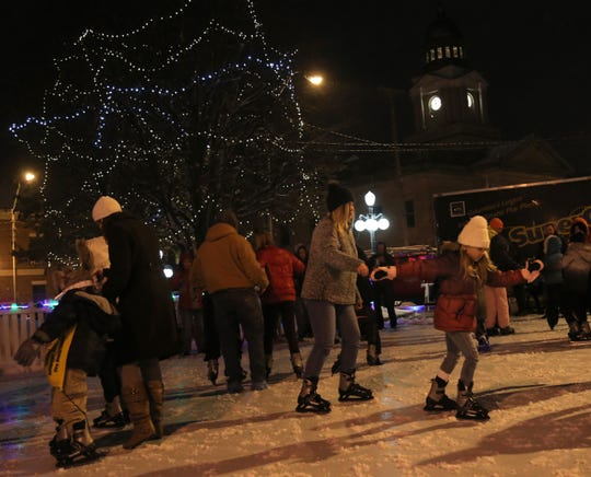 Children and adults skate on the temporary ice rink set up on Washington Square during the Candle Light Christmas in downtown Bucyrus on Thursday.