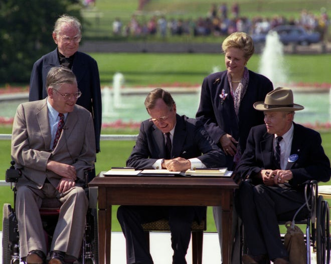 President Bush signs the Americans with Disabilities Act on the South Lawn of the White House on July 26, 1990. With him are the  Rev. Harold Wilkie of California, standing at left;  Sandra Parrino of the National Council on Disability, standing right;  Evan Kemp, Chairman of Equal Opportunity Commission, seated left; and Justin Dart of the Presidential Commission on Employment of People with Disabilities.