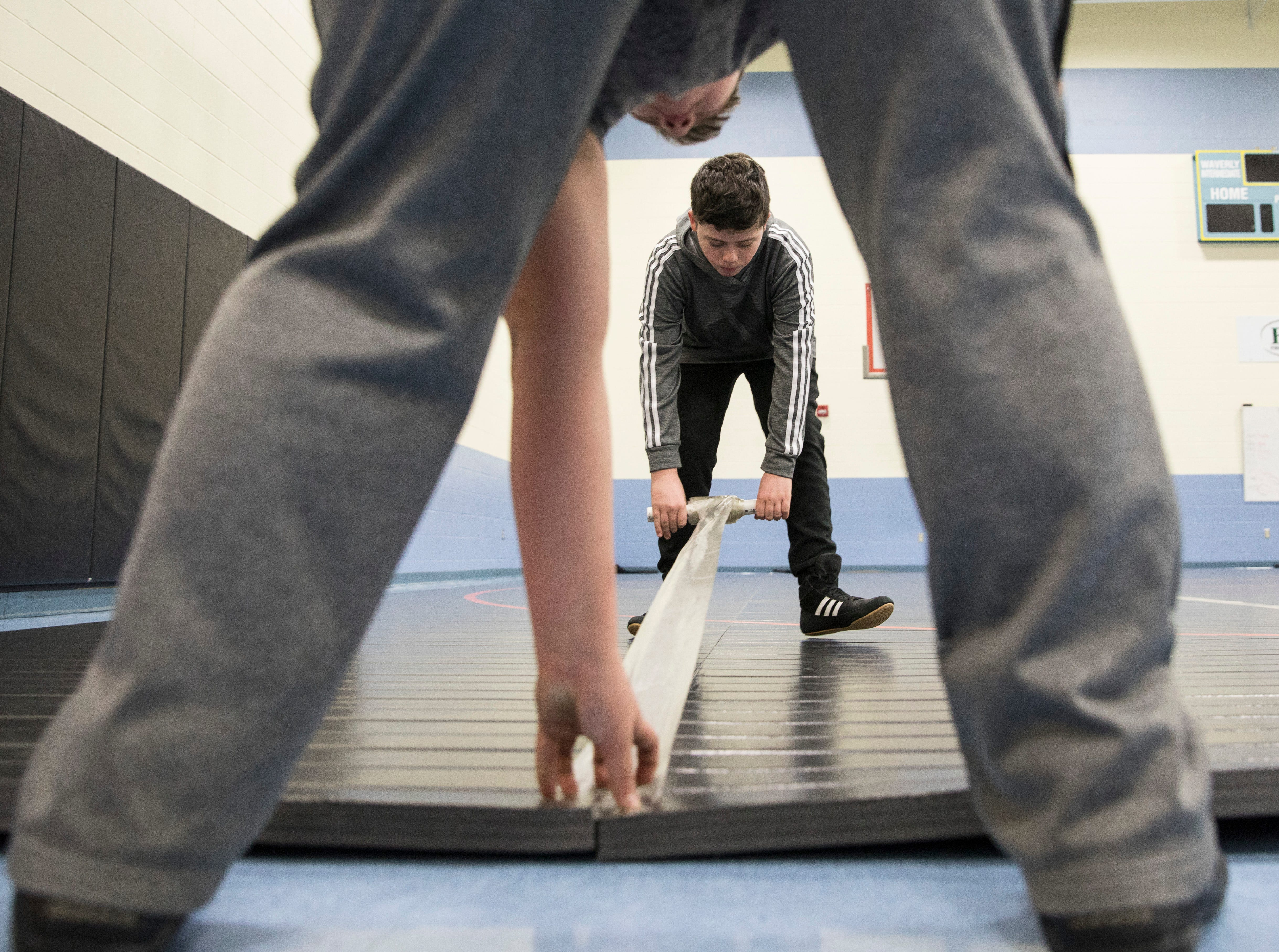 Reid Montgomery and William Madden come early to practice to help tape mats together so the wrestlers can start practice at five at Waverly Intermediate School Thursday afternoon.