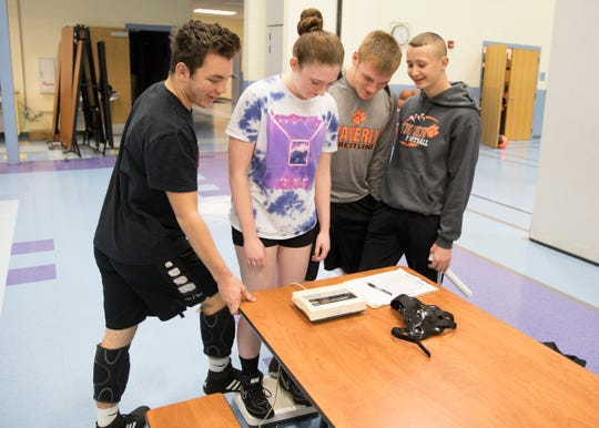 Trey Hamilton steps on the scale as several fellow wrestlers have fun with Abbi Montgomery as she tries to weigh herself before wrestling practice at Waverly Intermediate School Thursday afternoon.