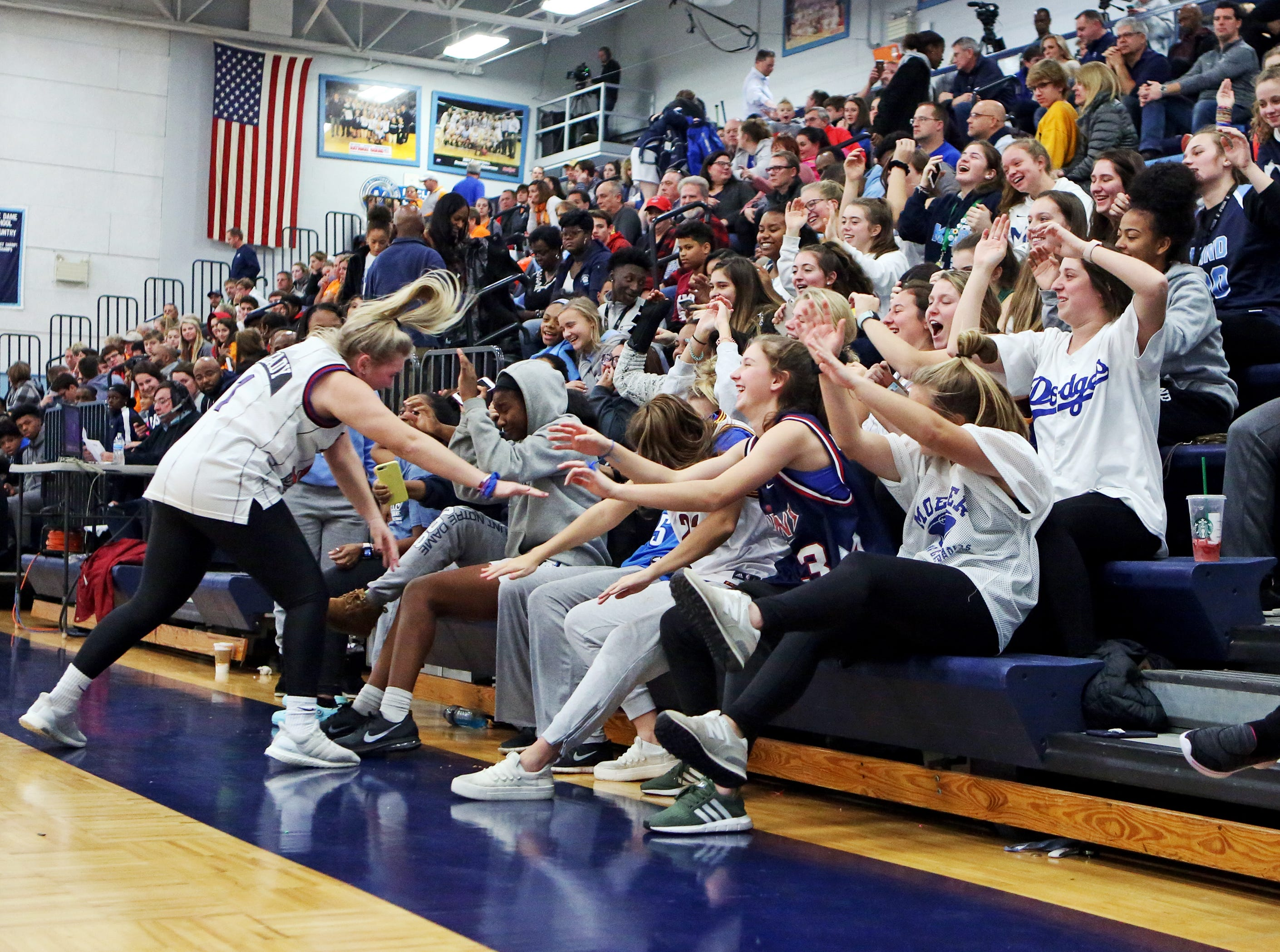 The MND student cheering section goes for a roller coaster ride. Mount Notre Dame defeated Mercy-McAuley 53-32.