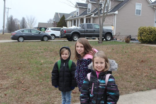The three younger Boyett girls, including (from left) 6-year old Savannah, 10-year old Paige, and 8-year old Andrea, wait in their driveway for their school bus. Their older sister Addison leaves an hour earlier on the middle school bus.