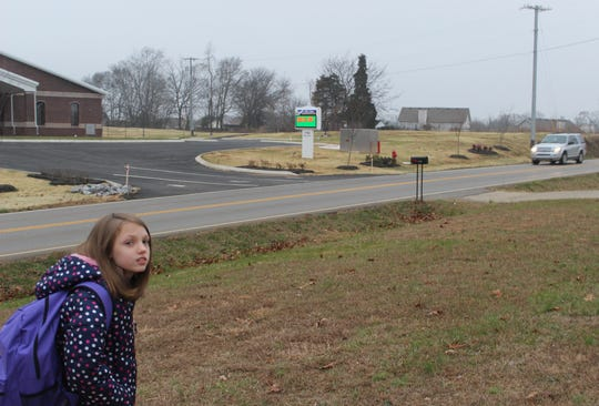 10-year old Paige Boyette waits at her bus stop as a car speeds by on Needmore Road.