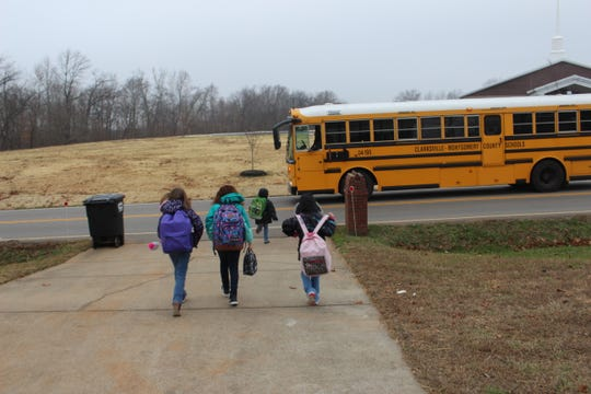 6-year old Savannah runs ahead of her sisters and neighbor after they've been given the signal to cross the street and board their school bus stopped on Needmore Road.