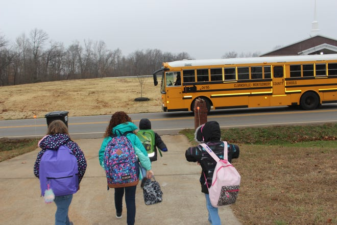 The Boyett girls walk with their neighbor to their school bus, after getting the go-ahead from their bus driver.