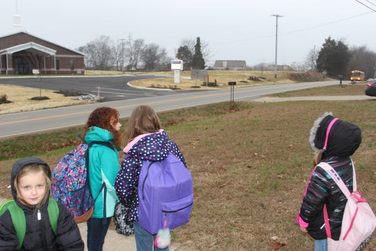 The Boyett girls and their next-door neighbor wait as their bus appears over the hill.