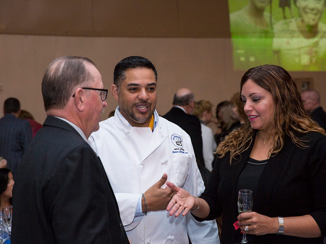 Tom Tighe, president of the board of directors of Camp Kiddie Keep Well in Middlesex  County, speaks with Chef Jaime Cresp of Les Marmitons and his wife, Rosa Crespo.