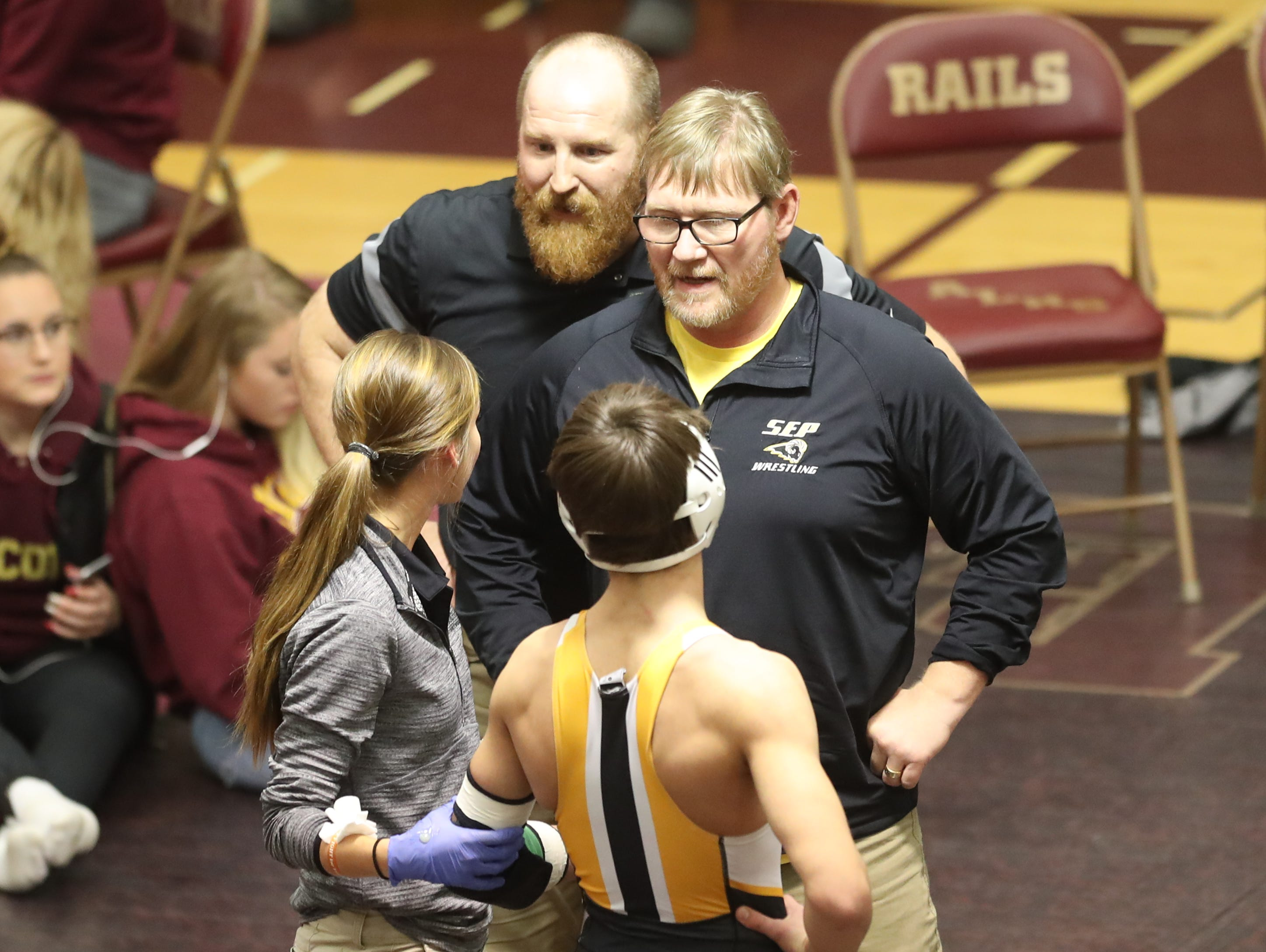 Dec 4, 2018; Des Moines, IA  USA; Joel Jesuroga (Southeast Polk) talks with the trainer and head coach Jason Christenson  during his match with DM Lincoln at Lincoln High School. The Rams beat the Railsplitters 66-6.