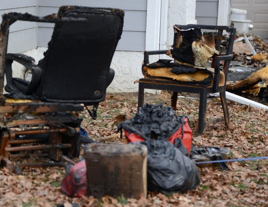 Burned furniture can be seen Friday, Dec. 7, 2018, outside a home at 825 41st St. in Des Moines, hours after a fire sent two people inside to the hospital for severe burns.