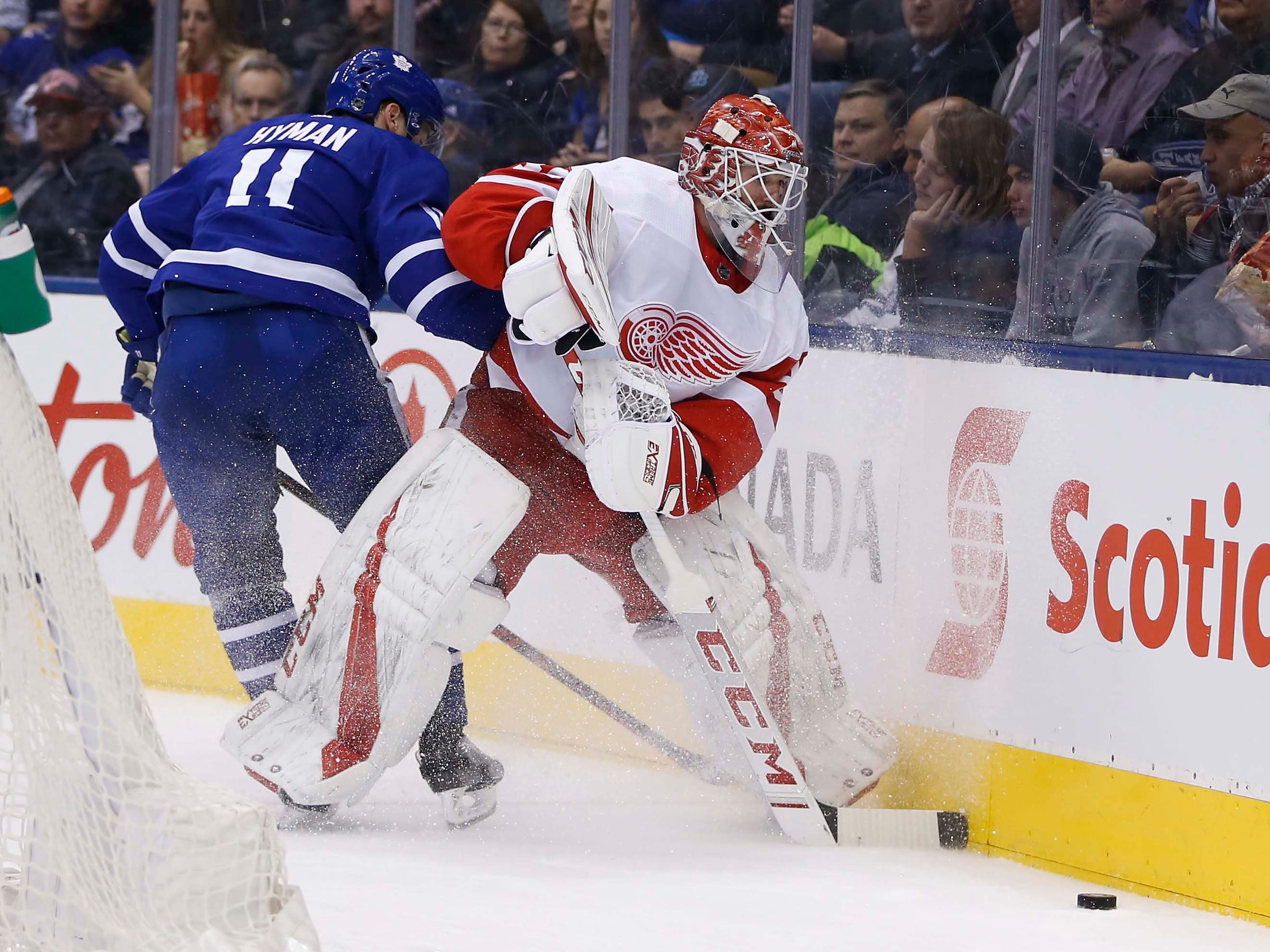 Detroit Red Wings goaltender Jonathan Bernier plays the puck while being pressured by Toronto Maple Leafs forward Zach Hyman during the second period at Scotiabank Arena, Dec. 6, 2018 in Toronto, Ontario, Canada.