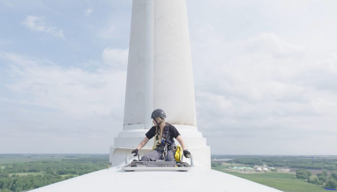 "Faith Lutat, wind school student, looks out from the top of a wind turbine in Iowa. From the film ""From Paris to Pittsburgh."""