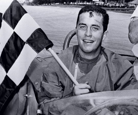 Roger Penske of Gladwyne, Pa., displays the checkered flag after he won the 100-mile race in the June sprints of the Road America in Elkhart Lake, Wis. on  June 19, 1961.