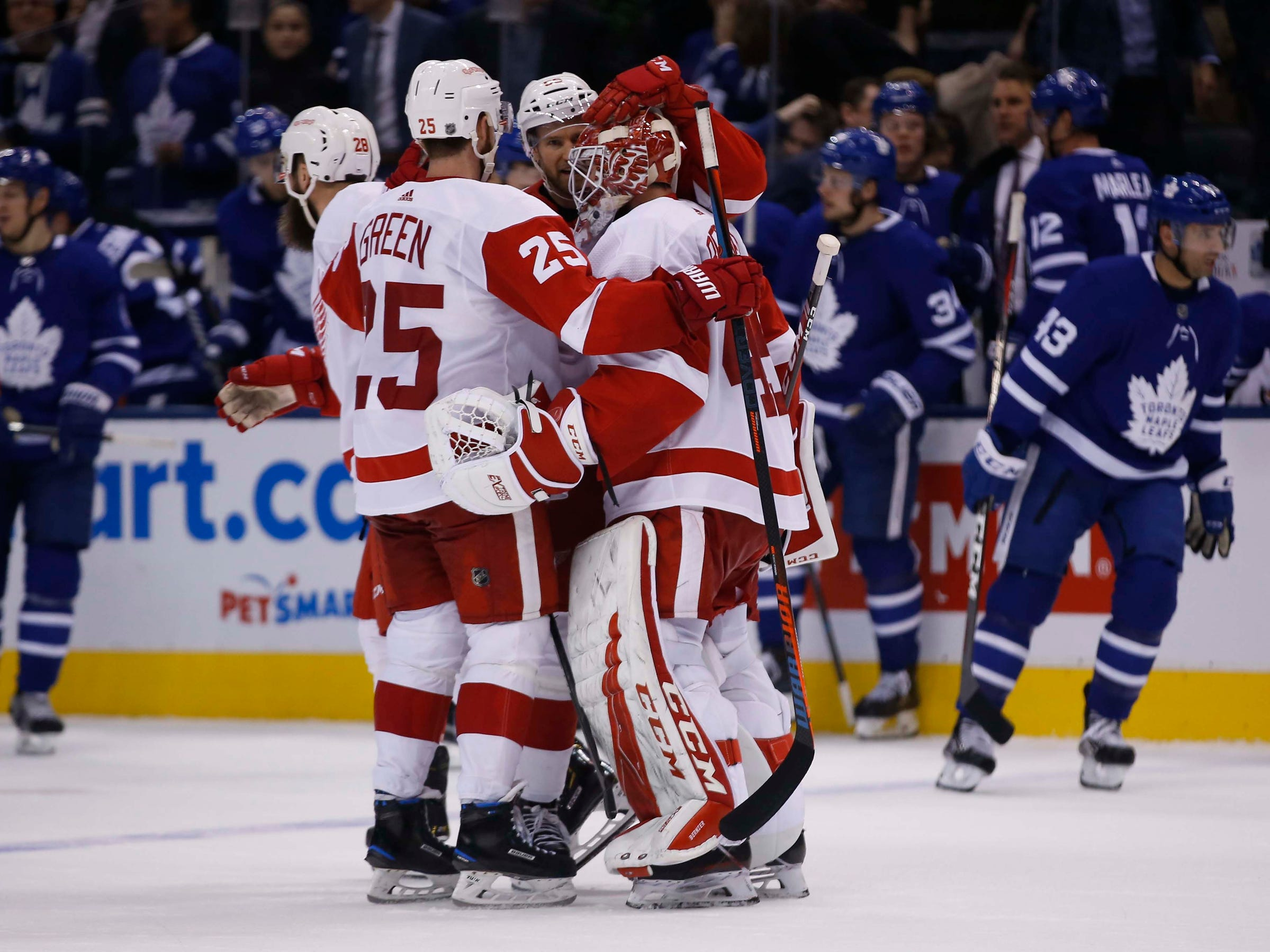 Detroit Red Wings' Mike Green (25) and goaltender Jonathan Bernier (45) celebrate a 5-4 OT win over the Toronto Maple Leafs at Scotiabank Arena, Thursday, Dec. 6, 2018.