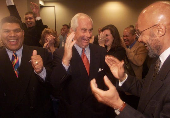 Larry Alexander, President of the Detroit Metro Visitor and Convention Bureau, (left) Head of Penske Corporation, Roger Penske, (center) Detroit Mayor Dennis Archer, (right) react as NFL Commissioner Paul Tagliabue announces that Detroit won its bid for the 2006 Super Bowl during the NFL owners meeting in Atlanta, GA in November 2000.
