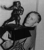 Former Army running back Pete Dawkins poses with the Heisman Trophy after winning it in 1958.