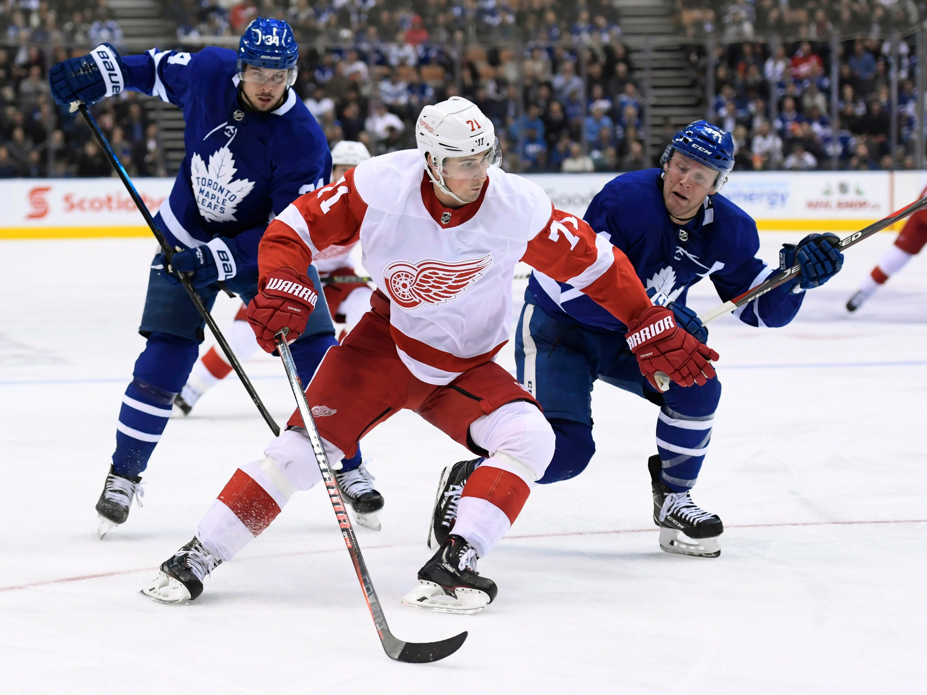 Red Wings center Dylan Larkin moves past Maple Leafs defenseman Morgan Rielly (44) as center Auston Matthews watches during the third period.