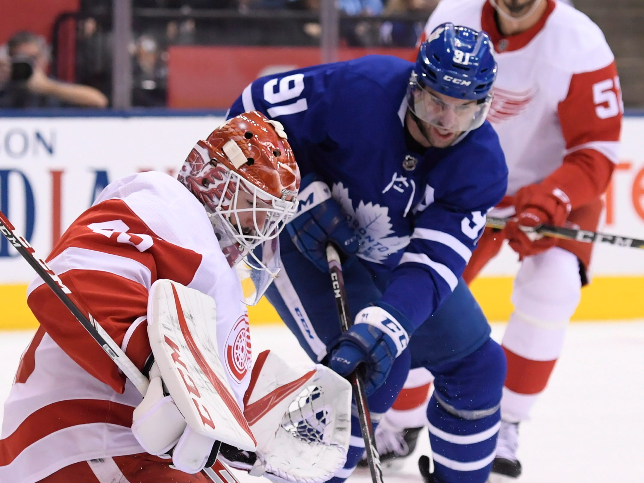 Maple Leafs center John Tavares (91) is stopped by Red Wings goaltender Jonathan Bernier as defenseman Jonathan Ericsson watches.
