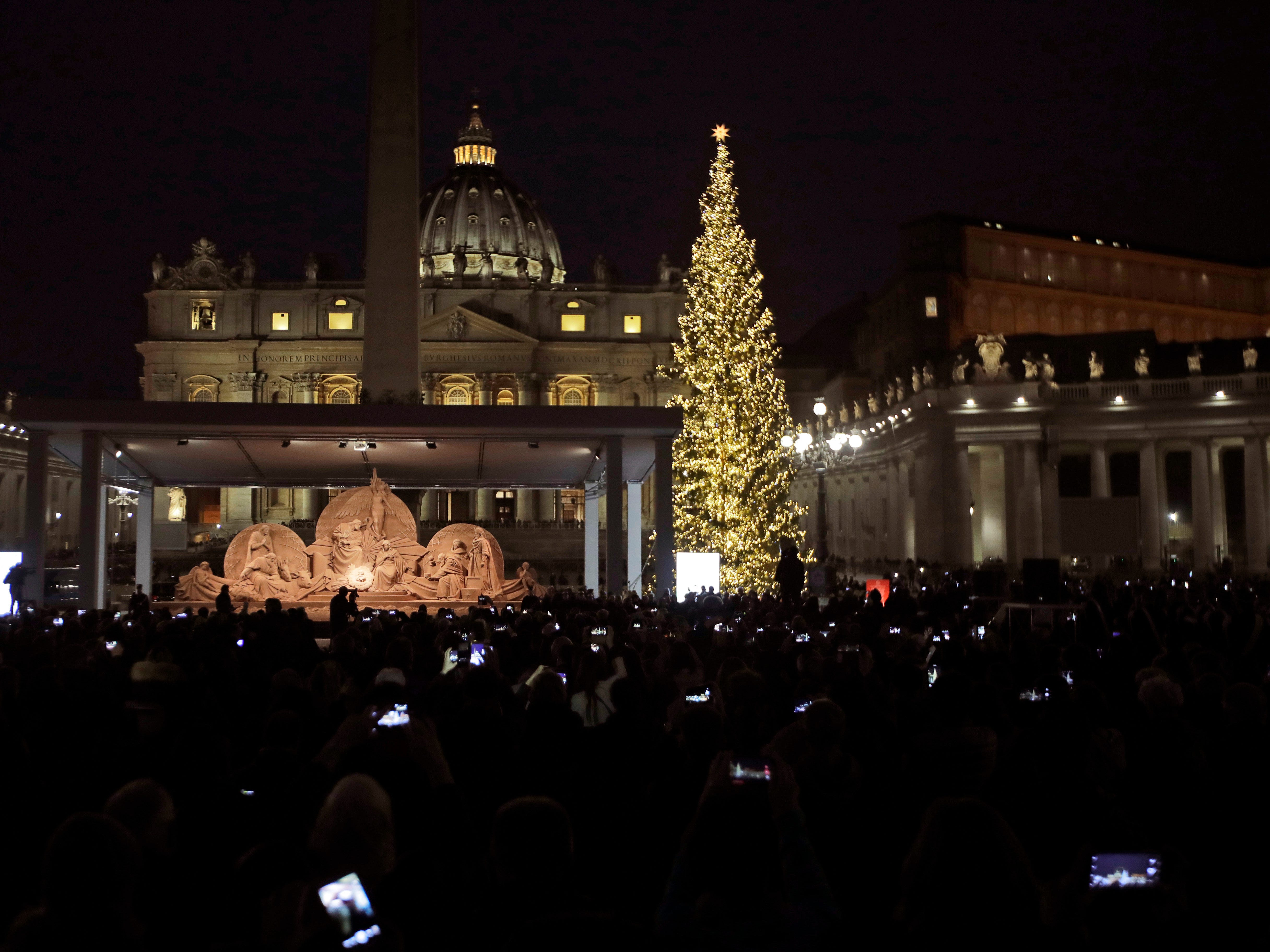A Nativity scene and a Christmas tree lights the foreground of St. Peter's Basilica during the official unveiling ceremony at the Vatican, Friday, Dec. 7, 2018. The Nativity scene was sculpted from about 700 tons of sand, and serves as the centerpiece of the Vatican's Christmastime decorations along with the giant tree.