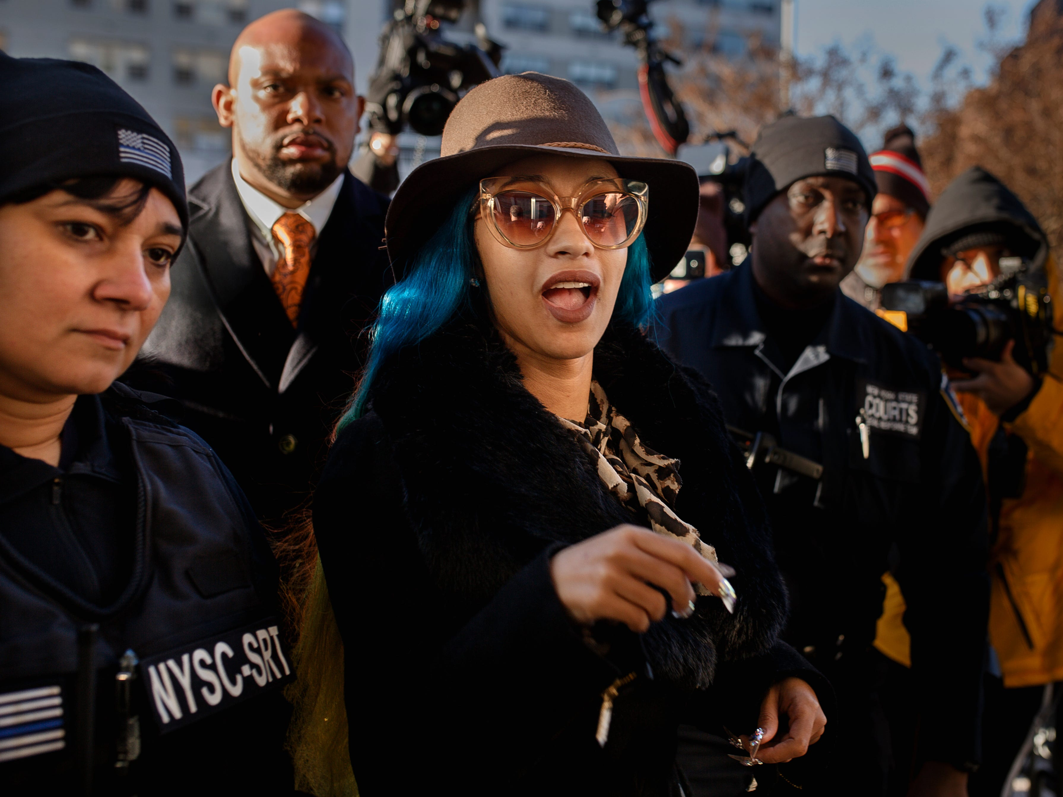 Rapper Cardi B, center, arrives at Queens County Criminal Court, Friday, Dec. 7, 2018, in New York. The platinum-selling hip hop star appeared in court on charges related to a brawl at a New York strip club.
