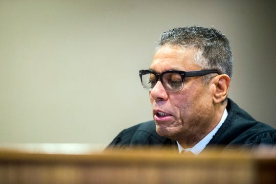 Genesee District Judge William Crawford reads through a prepared statement during a hearing on Dr. Eden Wells' involvement in the Flint water crisis, Friday, Dec. 7, 2018, at Genesee District Court in downtown Flint, Mich. Wells, Michigan's chief medical executive, will stand trial on involuntary manslaughter and other charges in a criminal investigation of Flint's water issues, Crawford ruled Friday.