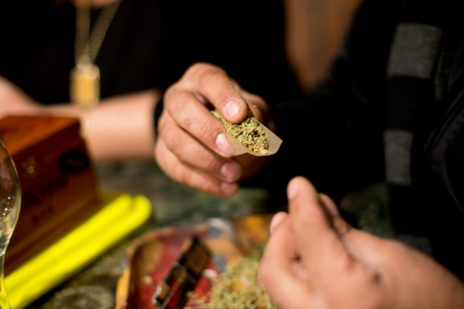 """Corey """"the Bud-Tender"""" rolls a joint at a party."""