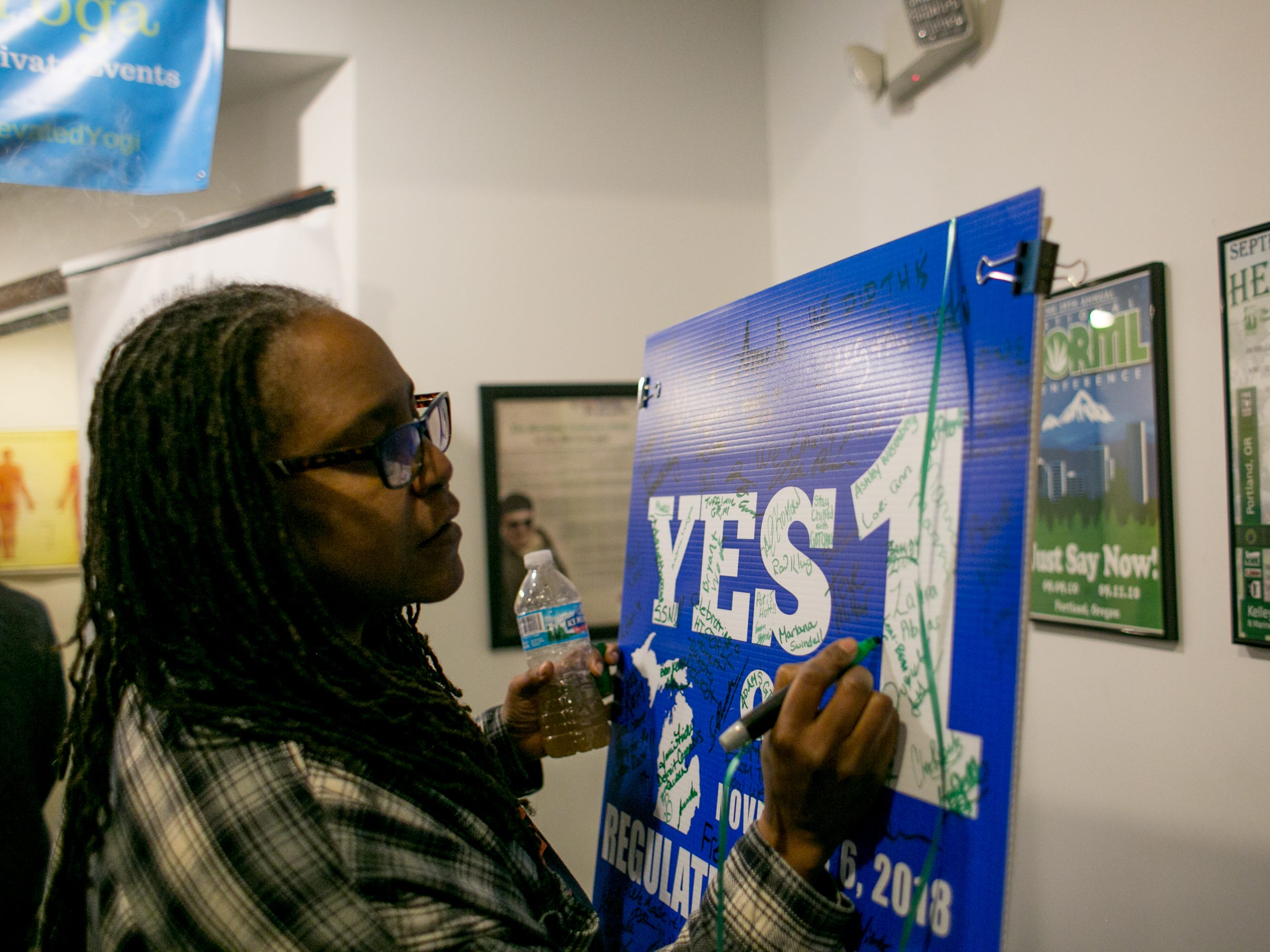 Lory Beth Coolidge, 50, of Detroit signs a poster at a party celebrating the first day of legal recreational marijuana use.