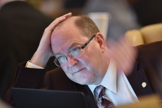 Sen David Robertson, R-Grand Blanc, listens closely to an aide before voting on a bill in May of 2017 at the Capitol in Lansing.