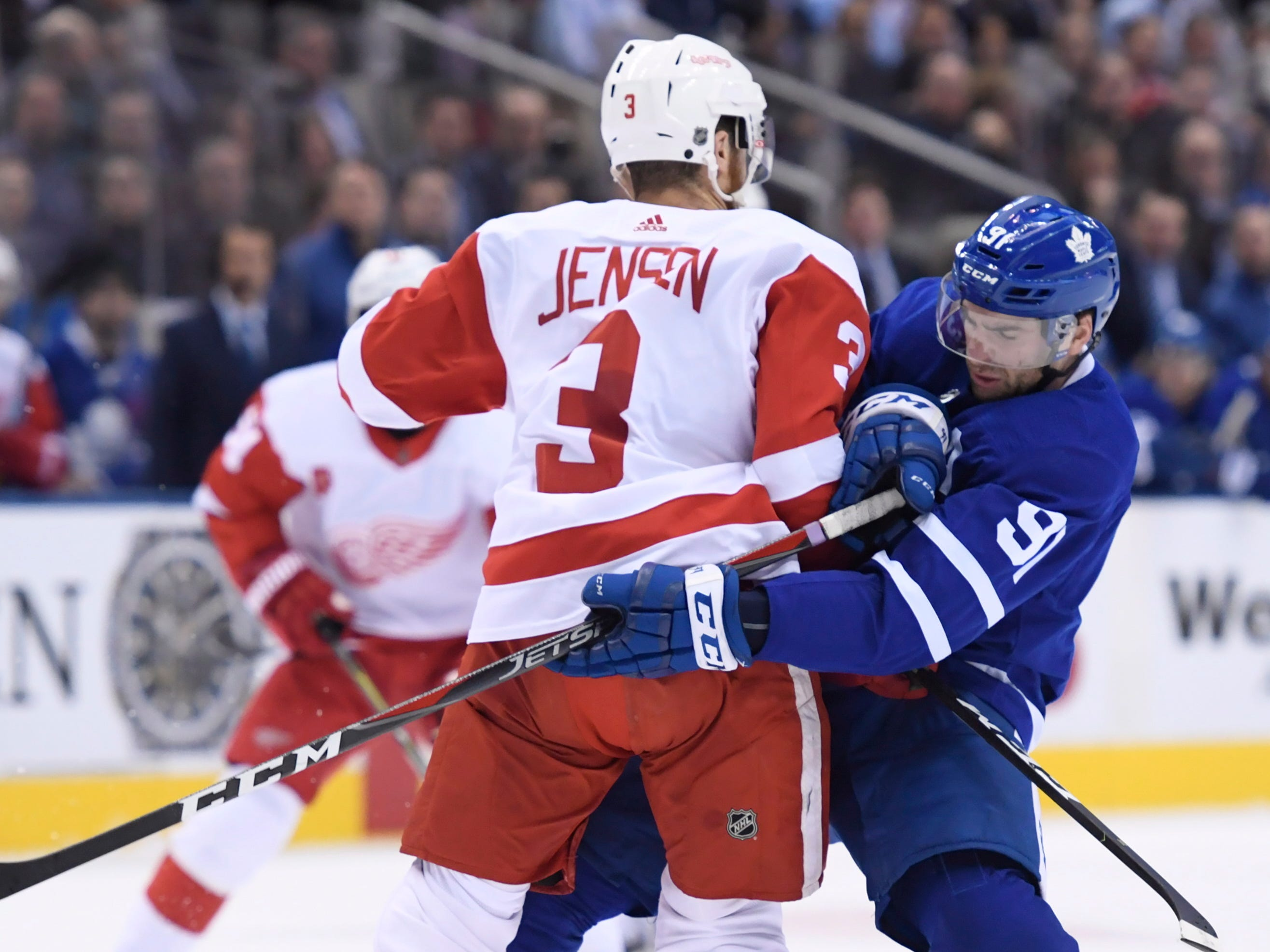 Maple Leafs center John Tavares (91) gets tied up with Red Wings defenseman Nick Jensen during the first period.