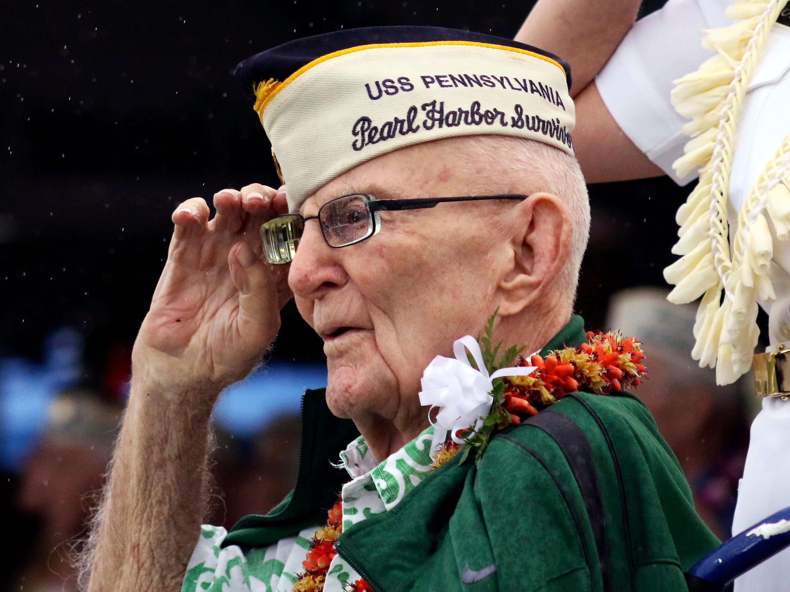 Everett Hyland, who survived the attack on Pearl Harbor as a crew member of the USS Pennsylvania, salutes on Friday, Dec. 7, 2018, as the USS Michael Murphy passes in Pearl Harbor, Hawaii during a ceremony marking the 77th anniversary of the Japanese attack. The Navy and National Park Service jointly hosted the remembrance ceremony at a grassy site overlooking the water and the USS Arizona Memorial.