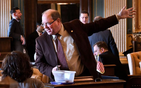 An animated Sen. David Robertson, R-Grand Blanc, waves his hands while talking with collegues as the Michigan Senate deliberated over a package of bills in February of this year.