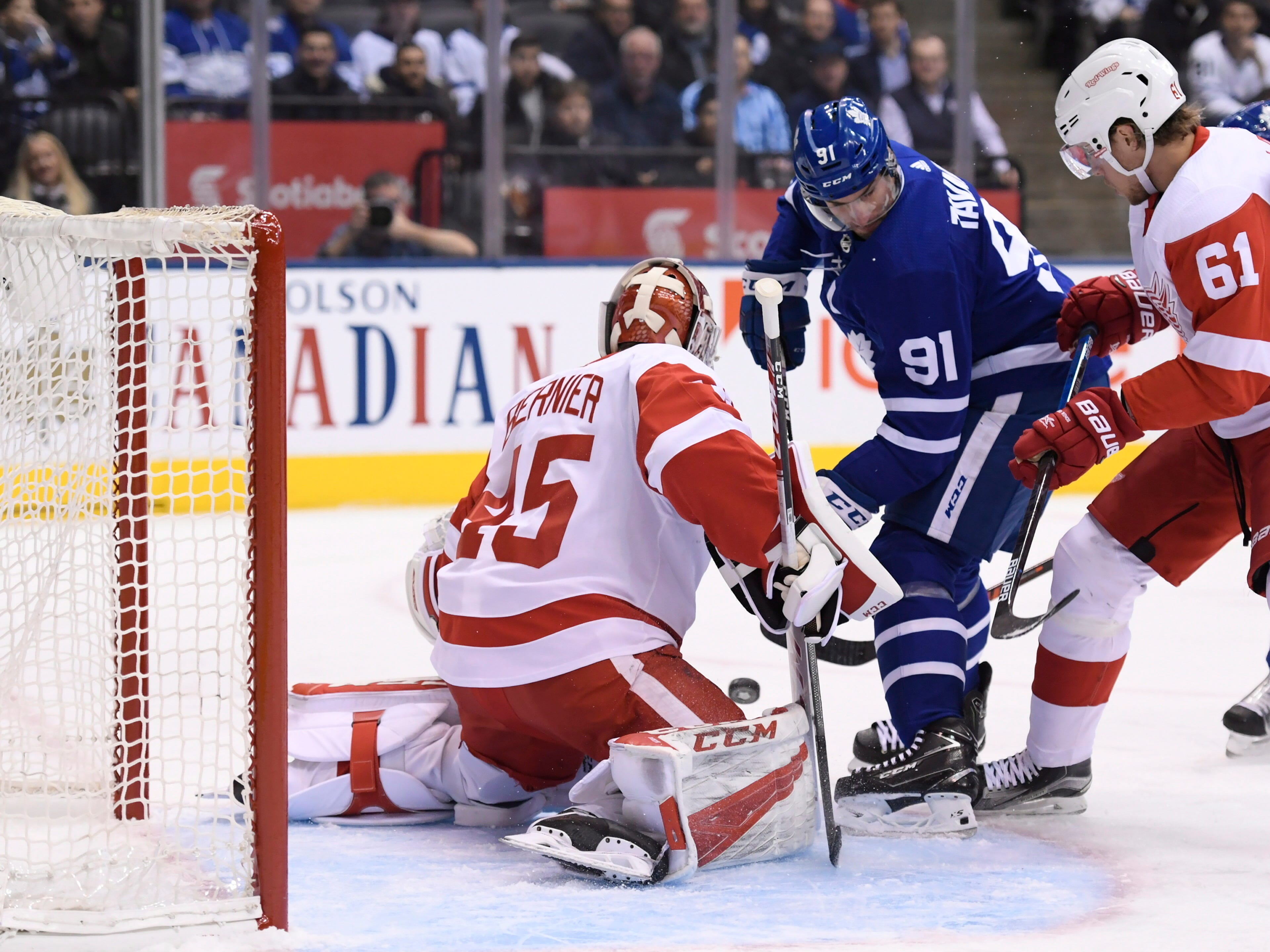 Maple Leafs center John Tavares is stopped by Red Wings goaltender Jonathan Bernier as center Jacob de la Rose moves in.