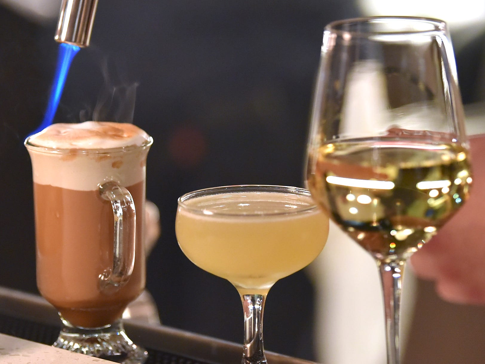 Bartender Jeffrey Urcheck of Hamtramck torches the top of a Fernet Meringue Swiss Holiday drink, left, next to an Evergarden cocktail, center, and a German semi-sweet glass of wine.
