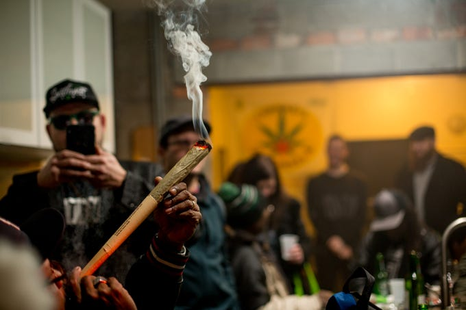 People smoke marijuana at a party celebrating the first day of legal recreational marijuana use, at the Cannabis Counsel on the east side of Detroit, Thursday night, Dec. 6, 2018.