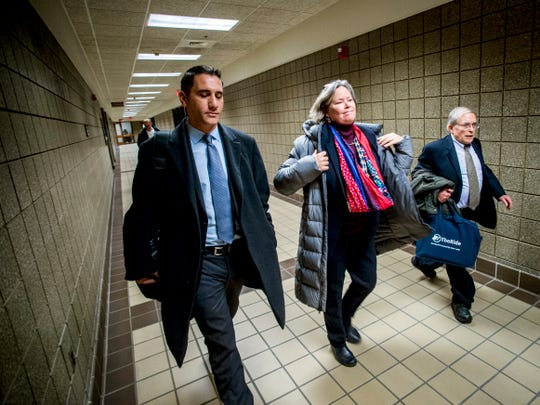 Dr. Eden Wells, center, puts her jacket on as she leaves the court house alongside her defense attorneys Steve Tramontin, left, and Jerold Lax after a hearing Friday, Dec. 7, 2018, at Genesee District Court in downtown Flint, Mich. Wells, Michigan's chief medical executive, will stand trial on involuntary manslaughter and other charges in a criminal investigation of the Flint water crisis, a judge ruled Friday.