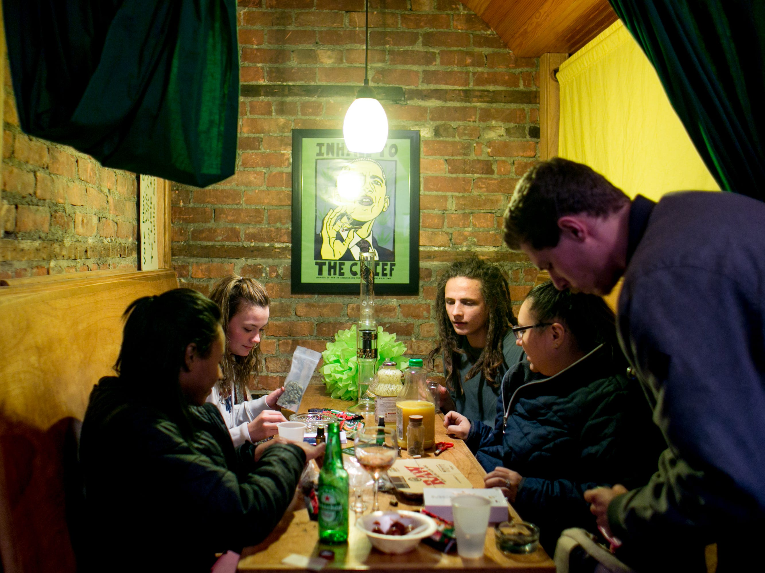 People gather in a restaurant-style booth at a party celebrating the first day of legal recreational marijuana use.