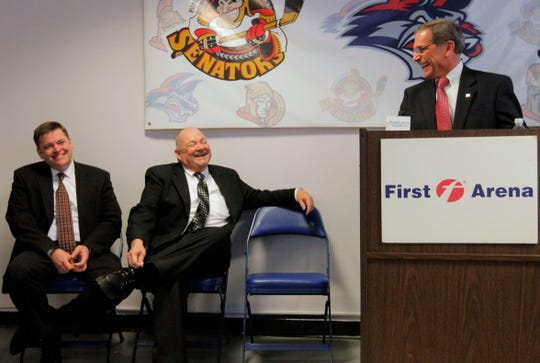 2013: Nathan Cook, left, and Tom Freeman, center, the new owners of the Elmira Jackals and who have a deal to own First Arena, smile as Chemung County Executive Tom Santulli speaks Wednesday at First Arena in Elmira.