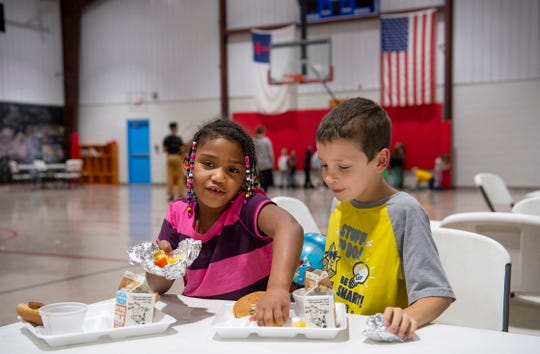 Bentley Wolfe, 7, offers up his canned fruit to Tiauna Williams, 6, at the Dream Center Thursday evening. The after school program offers kids a warm meal each day as well as exercise, fellowship and academic help.