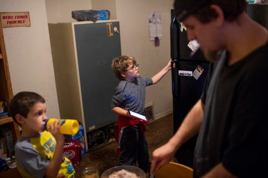 Kaleb Wolfe, 9, takes a look in the refrigerator while his dad, Cody Wolfe, right, mixes up brownie batter under the guidance of Bentley, 7, left, Thursday night.