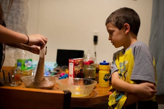 Kourtnie Wolfe, left, mixes up brownie ingredients under the watchful eyes of her son, Bentley, 7, Thursday night.