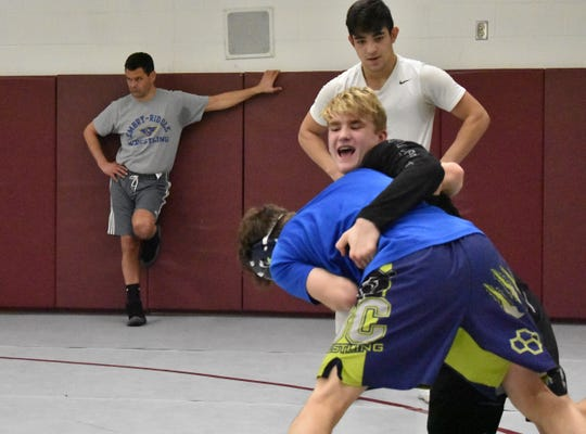 Vance VomBaur, facing, battles brother Will while Dominick Serrano and head coach Monte Trusty look on during a practice Wednesday at the school's wrestling room.